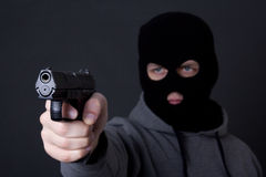 Man in black mask aiming with gun over grey Royalty Free Stock Image