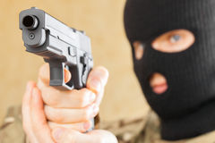 Man in black mask holding gun in front of him Royalty Free Stock Photography
