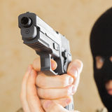 Man in black mask holding gun and ready to use it - studio shot Royalty Free Stock Image