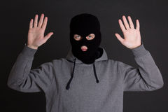 Man in black mask holding hands up over grey Royalty Free Stock Images