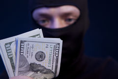 Man in black mask holding the money Royalty Free Stock Photography
