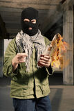 Man in black mask operating flammable bottle in hands Royalty Free Stock Photography