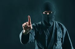 Man in black mask with pointing finger up. Copy space. Terrorism concept royalty free stock photos