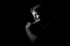 Man in black plays a flute Royalty Free Stock Photo