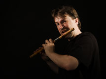 Man in black plays a flute Stock Photo