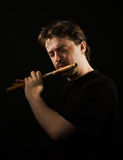 Man in black plays a flute Royalty Free Stock Photos