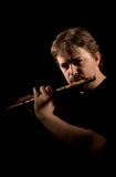 Man in black plays a flute Royalty Free Stock Photography