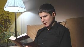 Man in black reading a book. 2 shots stock video footage