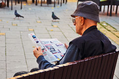 Man in black reads the newspaper Royalty Free Stock Photography