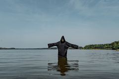 A man in a black robe with hands outstretched stands in the middle of the lake in warm weather. stock photos
