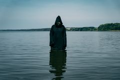 A man in a black robe with a hood stands in the river during the day. He mysteriously looks at the water. A man in a black robe with a hood stands in the river royalty free stock images