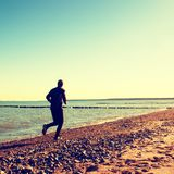 Man in black run  and exercise on beach at breakwater. Silhouette of tall man in black running  and exercising on stony beach at breakwater. Vivid and strong Stock Image