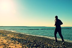 Man in black run  and exercise on beach at breakwater. Silhouette of tall man in black running  and exercising on stony beach at breakwater. Vivid and strong Stock Photo