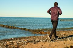 Man in black run  and exercise on beach at breakwater. Stock Images