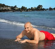 Man on Black sand beach. Mature man on a black sand beach on Big Island, Hawaii Royalty Free Stock Photography