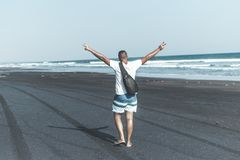 Man on the black sand beach. Bali island. Indonesia Royalty Free Stock Photos