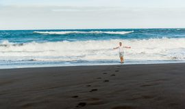 Man on the black sand beach. Happy man walking alone on the black sand beach of Tenerife island Royalty Free Stock Photo
