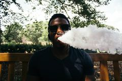 Man in Black Shirt Blowing Out Smoke Under Shade of Tree royalty free stock photography