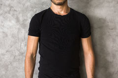 Man in black shirt closeup. Closeup of young man's body in empty black t-shirt on textured concrete wall background. Mock up Royalty Free Stock Images
