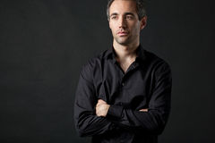 Man in black shirt on dark background in studio. Stock Images