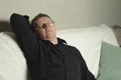 A man in a black shirt dozed off on the couch stock images