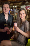 A man in a black shirt and a girl in a chaindress. A men in a black shirt and a girl in a chaindress with cocktails in the bar stock photography