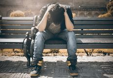 Man in Black Shirt and Gray Denim Pants Sitting on Gray Padded Bench royalty free stock images
