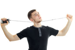 Man in black shirt with mobile phone and headphones in hands Royalty Free Stock Image