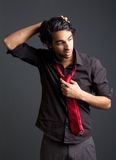 Man with black shirt and red tie posing with hand in hair Royalty Free Stock Photos