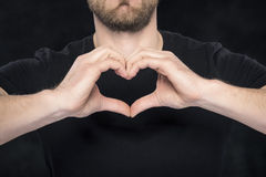 Man in a black shirt showing hand gesture heart Stock Photos