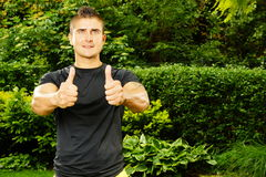 Man in black shirt shows thumb up. In the garden, right you can write some text Royalty Free Stock Photos