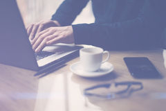 Man in black shirt working with laptop at sunny office.Modern notebook, cup of black coffee and smartphone on the wooden Stock Photography