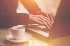 Man in black shirt working with laptop at sunny office.Modern notebook, cup of black coffee and smartphone on the wooden Royalty Free Stock Images