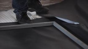 Man in black shoes and dark jeans stands on black sheet and grey metal frame. Man wearing black shoes and dark jeans stands on black sheet of some material next stock footage