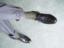 Man in black shoes. Man is sitting on his leg in gray trousers, brown socks and black shoes with laces Stock Photo