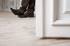 The man in black shoes on a wooden floor. The man in black shoes on a wooden floor closeup Royalty Free Stock Photo