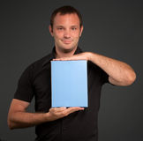 Man in black showing a blank package Stock Photos
