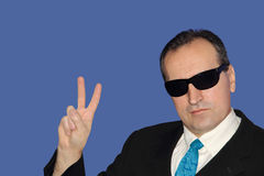 Man in black showing the victory sign. Man in black showing the victory sign on blue background Royalty Free Stock Images