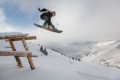 Man in Black Snowboard With Binding Performs a Jump Stock Photo