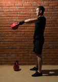 Man in black sportswear is engaged with a kettlebell of sports against the backdrop of a brick wall stock photos