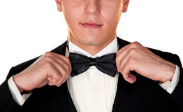 Man in a black suit adjusts his bow tie close-up face Royalty Free Stock Photography