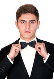 Man in a black suit adjusts his bow tie Stock Images