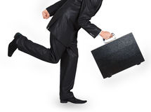 Man in a black suit with a black case running Royalty Free Stock Images