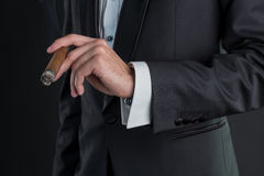 Man in a black suit with a cigar. Man in a black suit holding a cigar in a left hand Royalty Free Stock Photography