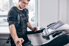 Man in black suit for ems training running on treadmill at gym. Ems training. Fit Man wearing black electromiostimulation suit preparing for running on treadmill Royalty Free Stock Photo