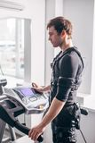 Man in black suit for ems training running on treadmill at gym. Fit Man in black electric muscle stimulation suit for ems training running on treadmill at gym Stock Image
