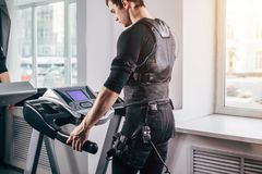 Man in black suit for ems training running on treadmill at gym. Fit Man in black suit for ems training preparing for running on treadmill at gym Stock Photography