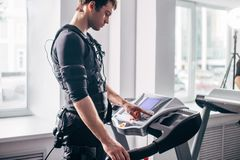 Man in black suit for ems training running on treadmill at gym. Ems training. Fit Man wearing black electromiostimulation suit preparing for running on treadmill Stock Photo