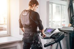 Man in black suit for ems training running on treadmill at gym. Ems training. Fit Man wearing black electromiostimulation suit preparing for running on treadmill Stock Photography