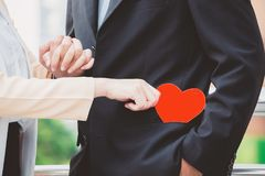 A man in a black suit with a handshake. A woman holds a red pape. R heart in his pocket. The concept of love Valentine`s Day stock photography